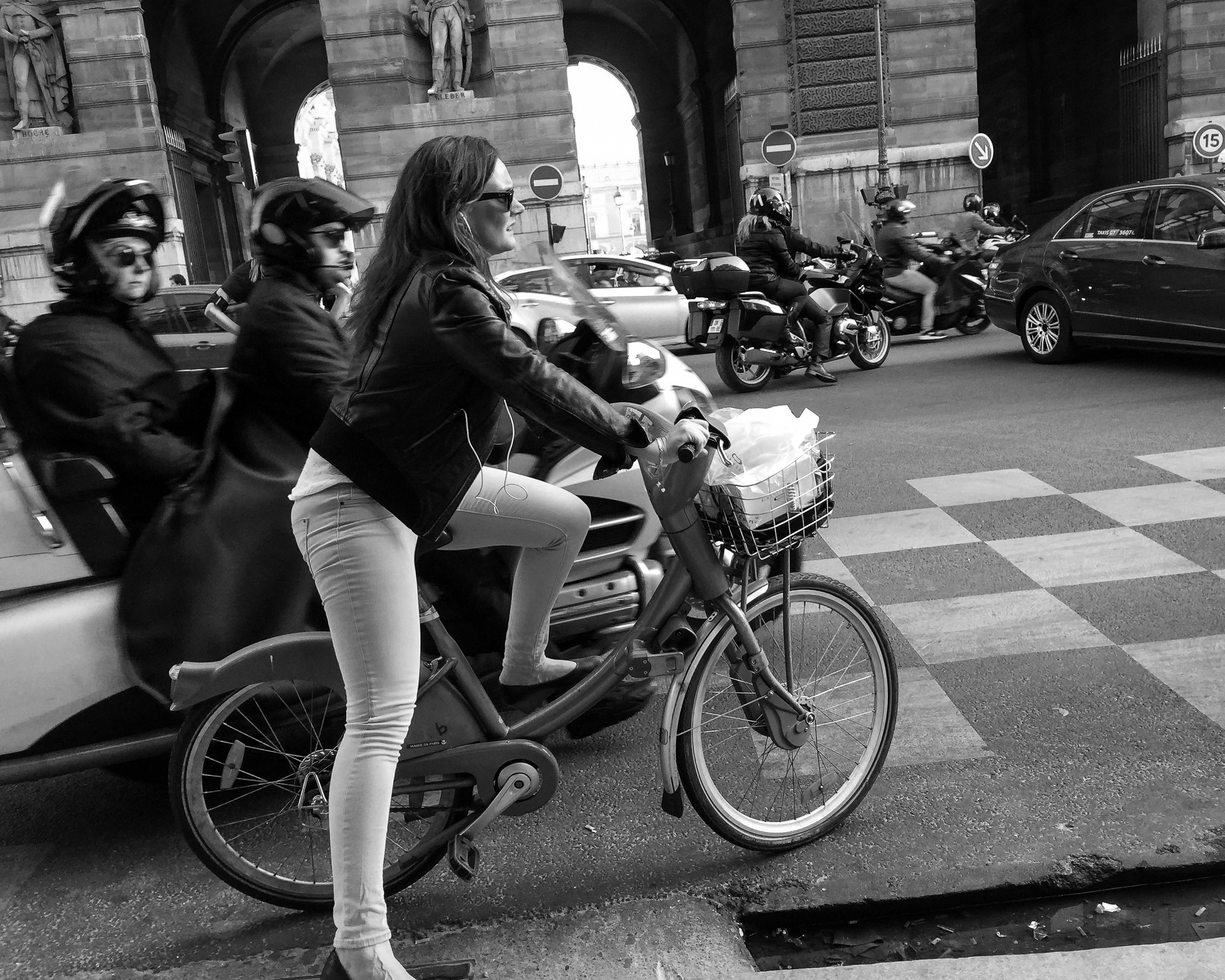 A woman rides a rented bike on the street in Paris, France. The Velib´ bike sharing program makes over 20,000 bikes available to Parisians at over 1,800 stations throughout the city.