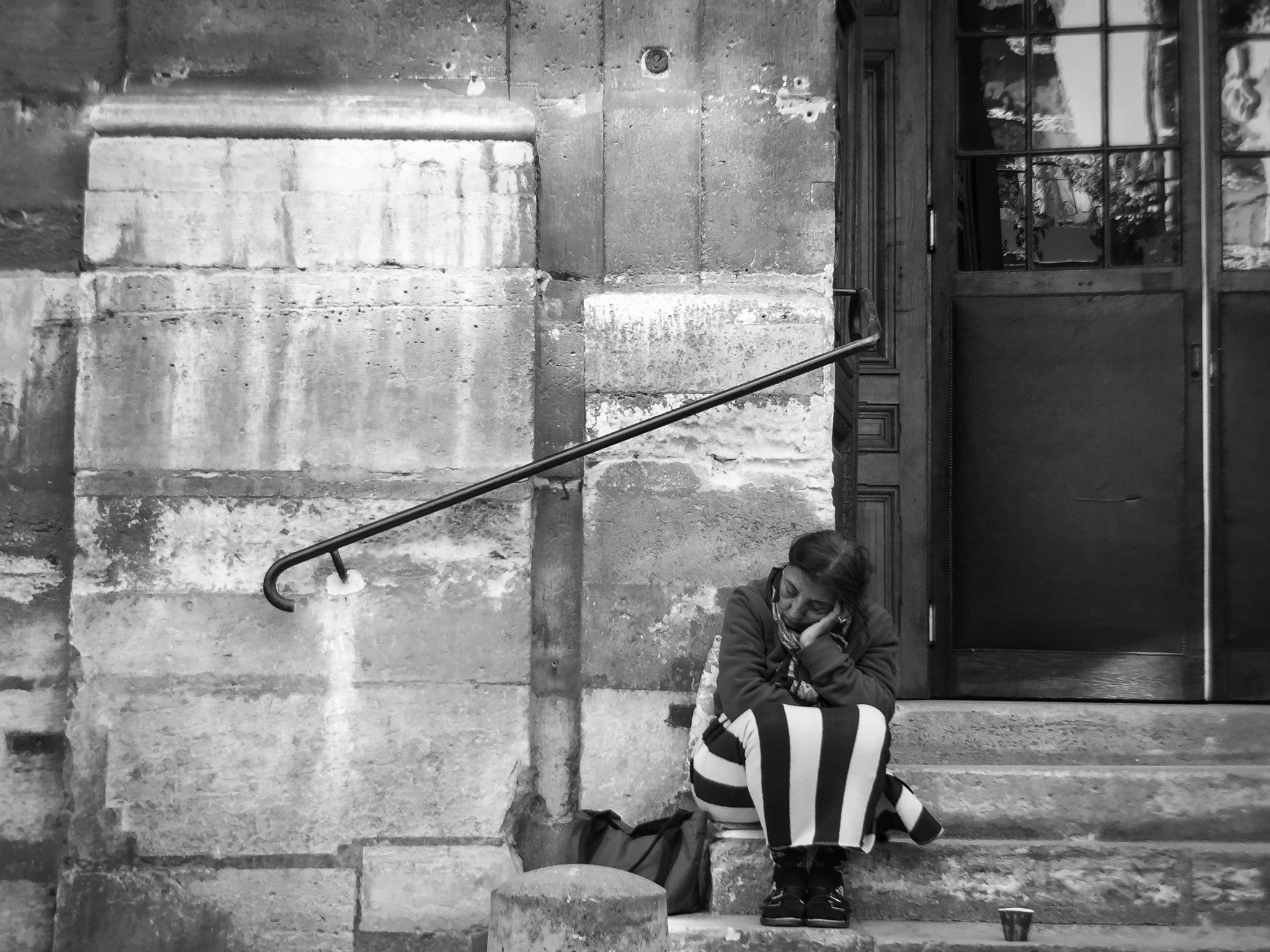 A woman begs for money on the steps of a church in Paris, France.