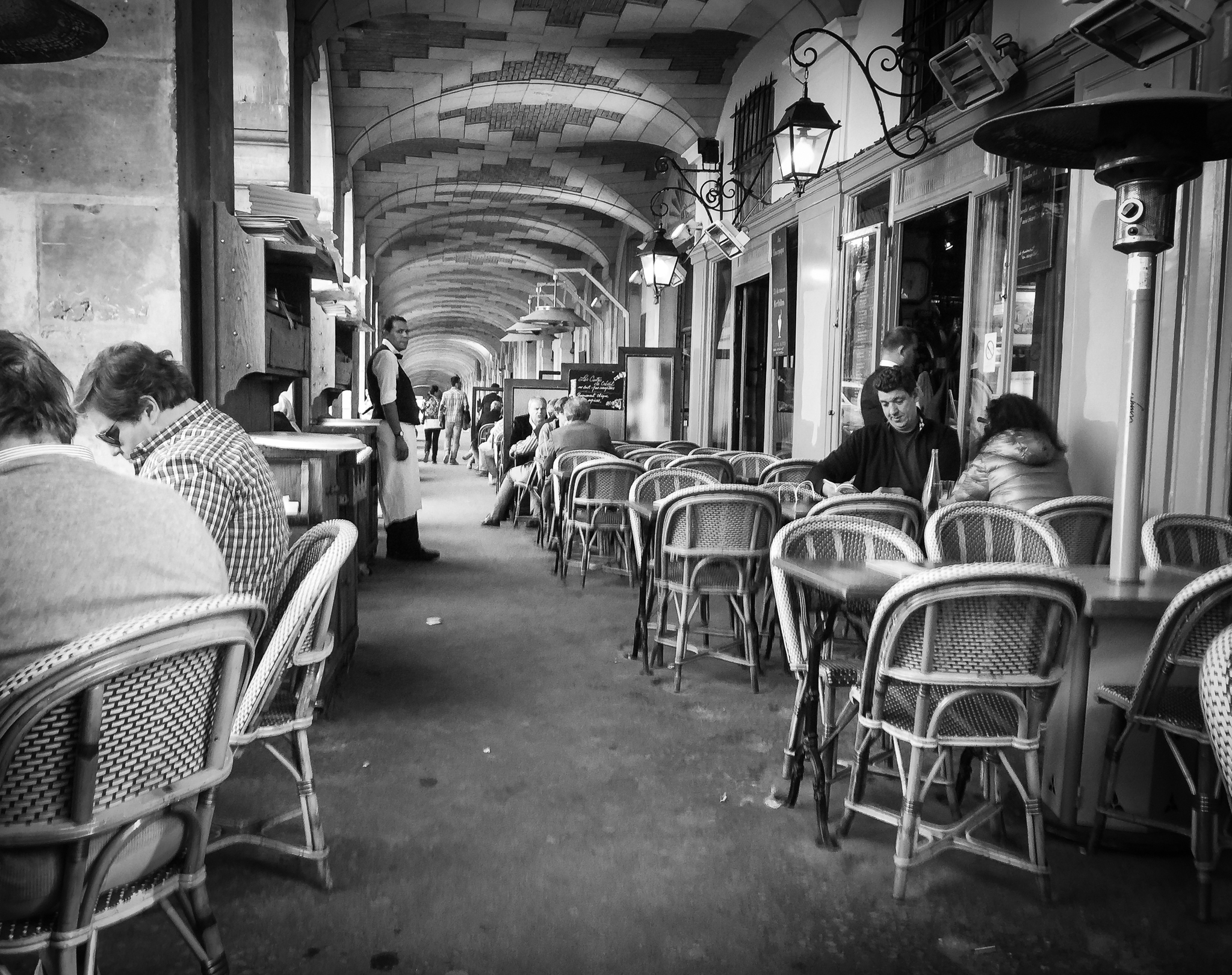 A waiter and his tables at cafe in Paris, France.