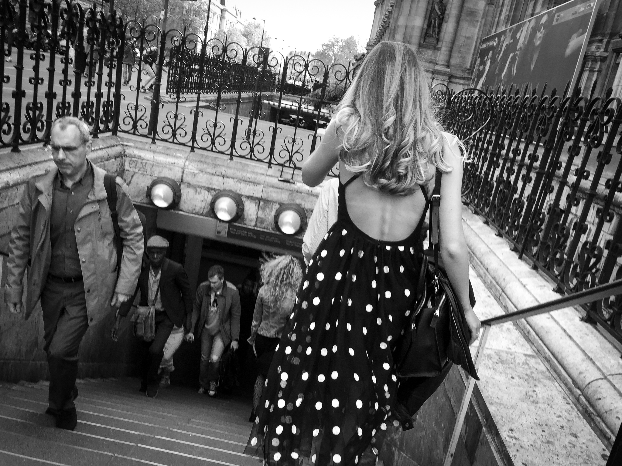 A woman wearing a polka dot dress enters the metro in Paris, France.
