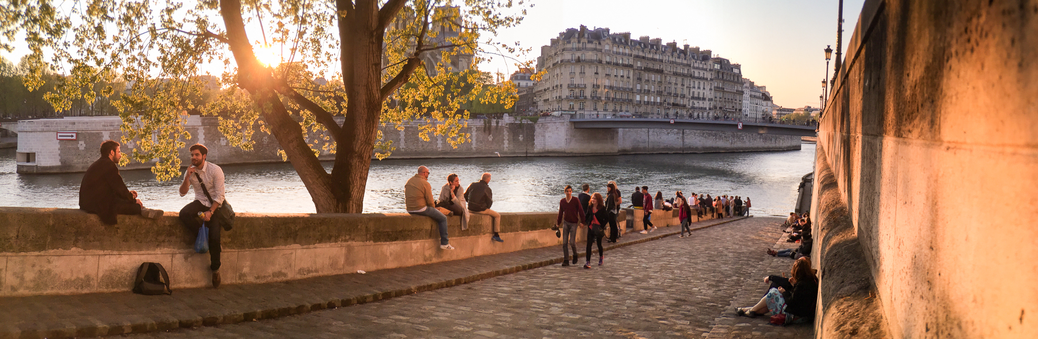Friends and couple crowd the banks of the Seine River during sunset in Paris, France.